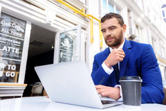 Male sitting outside of a cafe with computer. Bearded man working on laptop and drinking tea outdoors Stock Photos