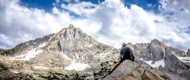 Male sitting on rocks in front of a high rocky mountain shot in a panoramic view royalty free stock images