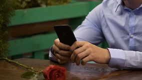 Male sitting at table using cellphone, red rose lying in front, waiting for date. Stock footage stock footage