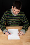 Male sitting by table with white paper. Photo male sitting by table with white paper Royalty Free Stock Photography