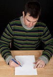 Male sitting by table with white paper. Photo male sitting by table with white paper Stock Photos