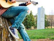 Male sitting on tree stump playing guitar. Ripped jeans, blue shoes stock image