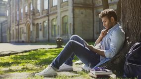 Male sitting under tree, using mobile phone, reacting to newsfeed, confusion. Stock footage Stock Photography