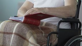 Male sitting wheelchair, opening photo album to look at pictures, past memories