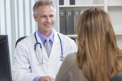 Male sjukhusdoktor Talking till kvinnligtålmodign Arkivbild