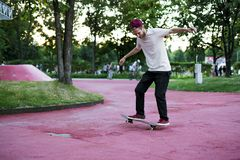 Male skateboarder doing crazy tricks in the city street park on a summer day stock image