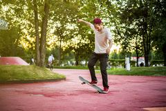Male skateboarder doing crazy tricks in the city street park on a summer day. Outdoors Royalty Free Stock Image