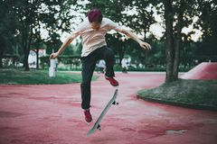 Male skateboarder doing crazy tricks in the city street park on a summer day. Outdoors Stock Photo