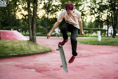 Male skateboarder doing crazy tricks in the city street park on a summer day. Outdoors Stock Images