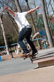 Male Skateboarder Grinding. Action shot of a skateboarder performing a jump at a skate park Stock Photography
