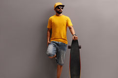 Male skater holding a longboard. Male skater with a yellow cap holding a longboard and leaning against a gray wall Stock Photo