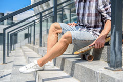 Male skater with skateboard on stairs. Sporty young man is sitting on steps and holding skate Royalty Free Stock Image