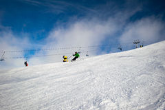 Male skier carving down an Australian ski slope. On a cloudy day. Dormant snow guns and a chair lift can be seen in the background Royalty Free Stock Photography