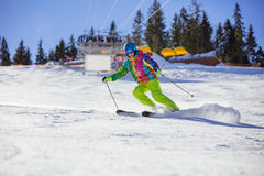 Male skier carving turn on mountain slope. Chairlift in background Royalty Free Stock Images