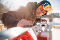 Male skier checks skis before skiing, winter sport. Male skier checks skis before skiing, closeup. Winter active sport, extreme lifestyle. Downhill skiing Royalty Free Stock Photo