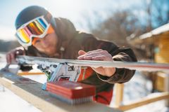 Male skier checks skis before skiing, winter sport. Male skier checks skis before skiing, closeup. Winter active sport, extreme lifestyle. Downhill skiing Royalty Free Stock Photography