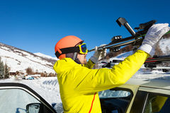 Male skier fastening skis to roof rails of car. Portrait of active male skier fastening skis to roof rails of car at snowy mountains Royalty Free Stock Photo