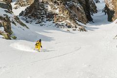 A male skier freerider with a beard descends the backcountry at high speed from the slope. Leaving a trail of snow powder behind him against the background of Royalty Free Stock Photography