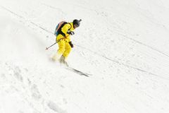 A male skier freerider with a beard descends the backcountry at high speed from the slope. Leaving a trail of snow powder behind him. The concept of freeriding Royalty Free Stock Photo