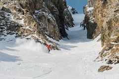 A male skier freerider with a beard descends the backcountry at high speed from the slope. Leaving a trail of snow powder behind him against the background of Royalty Free Stock Images
