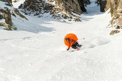 A male skier freerider with a beard descends the backcountry at high speed from the slope. Leaving a trail of snow powder with the opened anti-avalanche pillow Stock Image