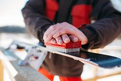 Skier prepares his skis for riding, winter sport. Male skier hands prepares skis for riding. Winter active sport, extreme lifestyle. Downhill skiing Stock Images