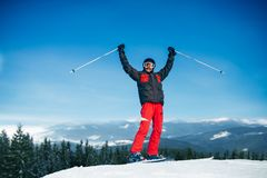 Male skier hands up on the top of mountain. Blue sky, forest and snowy mountains on background. Winter active sport, extreme lifestyle. Downhill skiing Stock Photography