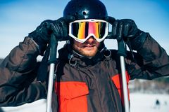 Male skier in helmet puts on glasses, front view. Winter active sport, extreme lifestyle. Downhill skiing Stock Image