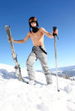 Male skier holding skis and ski poles. On snow-covered slope of mountain Stock Image