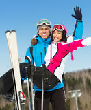 Male skier holds woman in his arms. Male skier holds women wearing sports jacket and goggles in his arms Royalty Free Stock Images