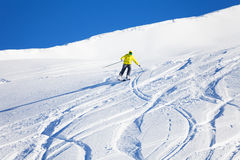 Male skier running downhill on slope at sunny day. Portrait of male skier running downhill on slope at sunny day Royalty Free Stock Images