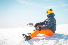 Male skier sitting on snow relaxing looking in the distance Stock Images