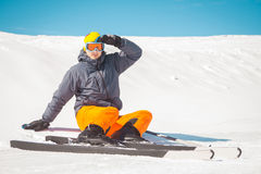 Male skier sitting on snow relaxing looking at the piste. Man skier sitting on snow relaxing looking at the piste Royalty Free Stock Image