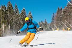 Skier riding in the mountains on a sunny winter day. Male skier skiing in the mountains copyspace ski resort. Blue sky and winter forest on the background Royalty Free Stock Image