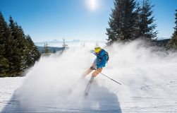 Skier riding in the mountains on a sunny winter day. Male skier skiing on the slope at ski resort in the mountains copyspace sports recreation winter people Royalty Free Stock Photo