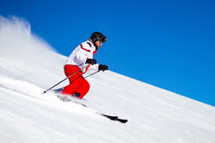 Male Skier Speeding Down Ski Slope. Expert male skier wearing red ski trousers skiing down a steep slope. Trademarks have been removed Royalty Free Stock Image