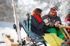 Male skier toasting with female skier. In cafe on ski terrain Stock Photos