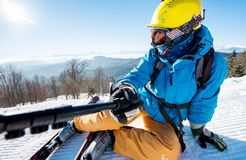 Male skier using selfie stick taking photos while skiing Stock Image