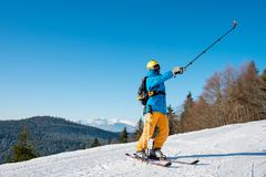 Male skier using selfie stick taking photos while skiing. Full length shot of a male skier taking a selfie using selfie stick posing on the slope Royalty Free Stock Photo