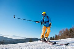 Male skier using selfie stick taking photos while skiing. Full length shot of a skier standing on top of a mountain on a beautiful sunny winter day taking a Royalty Free Stock Photos