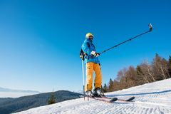 Male skier using selfie stick taking photos while skiing Stock Images