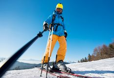 Male skier using selfie stick taking photos while skiing. Low angle shot of a male skier taking a selfie using selfie stick posing on top of a slope at the Royalty Free Stock Images