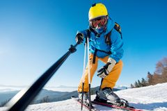 Male skier using selfie stick taking photos while skiing. Low angle shot of a professional skier taking a selfie using monopod posing on top of a slope in the Royalty Free Stock Photography