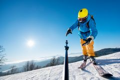 Male skier using selfie stick taking photos while skiing. Male skier dropping his camera on monopod while taking a selfie in the mountains failure concept Royalty Free Stock Images