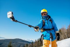 Male skier using selfie stick taking photos while skiing. Male skier taking a selfie using his action camera and monopod in winter sunny day at ski resort Stock Photos