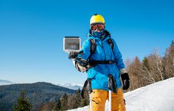 Male skier using selfie stick taking photos while skiing. Male skier taking a selfie using his action camera and a selfie stick technology recreation activity in Stock Photo