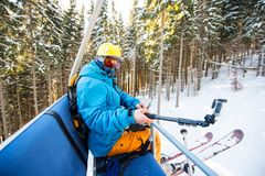 Male skier using selfie stick taking photos while skiing. Male skier taking selfies with action camera on selfie stick while riding up on ski lift in the Royalty Free Stock Image