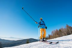 Male skier using selfie stick taking photos while skiing. Professional skier standing on top of a mountain on a beautiful sunny winter day taking a selfie with Stock Photo