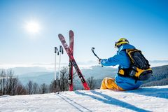 Male skier using selfie stick taking photos while skiing Royalty Free Stock Photography