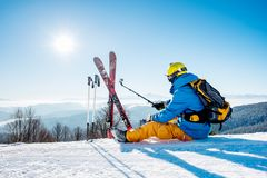 Male skier using selfie stick taking photos while skiing. Rearview shot of a skier sitting on the snow on top of the mountain taking selfies with his action Stock Images